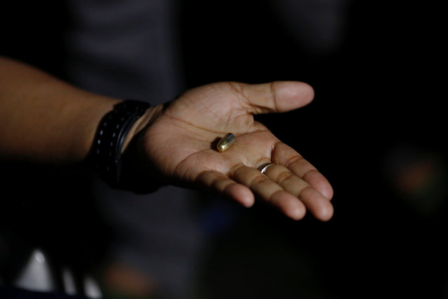 A police officer shows the bullet that he said was stopped by his body armour during a shootout with four alleged drug users in Manila, Philippines early October 14, 2016. (Photo by Damir Sagolj/Reuters)