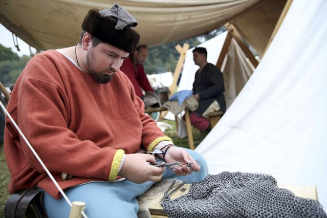 A re-enactor mends his chain mail before a re-enactment of the Battle of Hastings, commemorating the 950th anniversary of the battle, in Battle, Britain October 15, 2016. (Photo by Neil Hall/Reuters)