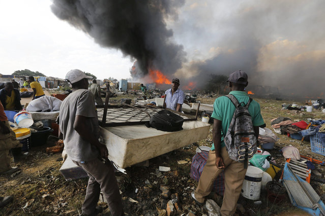 A man carries his bed as he and a friend tries to remove her belongings as a fire rages through an informal settlement in Kaya Sands, Johannesburg, 11 November 2015. The flames fueled by high winds and a heat waves swept through the shacks of the settlement. At least 250 shacks where distroyed. (Photo by Kim Ludbrook/EPA)