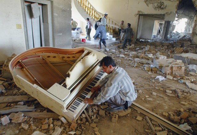A man plays piano in one of the palaces of ousted Iraq President Saddam Hussein in the Iraqi capital of Baghdad Saturday May 3, 2003, as others loot the palace. (Photo by Alexander Zemlianichenko/AP Photo)