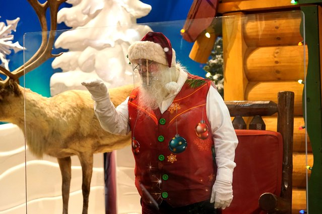 Santa Claus waves at children and their families from behind a transparent barrier at Bass Pro Shops, Friday, November 20, 2020, in Miami. This is Santa Claus in the Coronavirus Age, where visits are done with layers of protection or moved online. Putting hundreds of kids a day onto your lap to talk directly into your face — that's not happening. (Photo by Lynne Sladky/AP Photo)