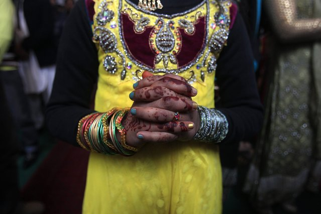 A girl with henna-dyed hands, attend a mass on Christmas day at the St John's Cathedral Church, in Peshawar December 25, 2014. (Photo by Fayaz Aziz/Reuters)