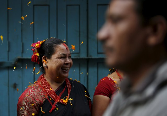 A Newari woman, dressed in traditional attire, smiles as she observes the Newari New Year parade that falls during the Tihar festival, also called Diwali, in Kathmandu, Nepal November 12, 2015. (Photo by Navesh Chitrakar/Reuters)