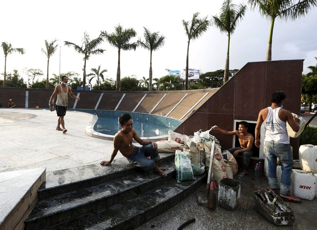 Men work on a fountain at a newly constructed, opening-soon, shopping mall in Yangon, Myanmar, November 11, 2015. (Photo by Olivia Harris/Reuters)