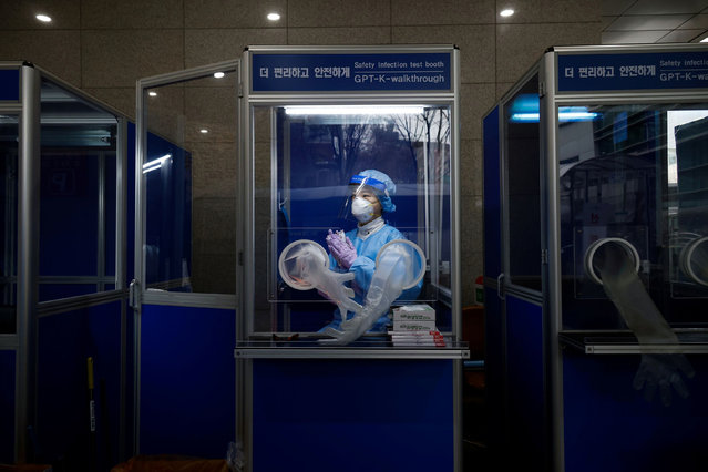 A medical worker keeps warm inside a booth as she prepares to conduct a coronavirus disease (COVID-19) test at a testing site in Seoul, South Korea, December 13, 2020. (Photo by Kim Hong-Ji/Reuters)