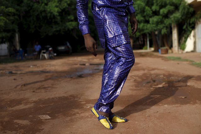 Bazin designer Baba Sereme poses for a picture in a bazin outfit he dyed, in front of his home in Bamako, Mali, October 8, 2015. (Photo by Joe Penney/Reuters)