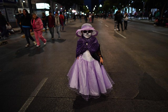 "A girl dressed as ""Catrina"" walks while taking part in the ""Catrinas Parade"" along Reforma Avenue, in Mexico City on October 23, 2016. (Photo by Yuri Cortez/AFP Photo)"