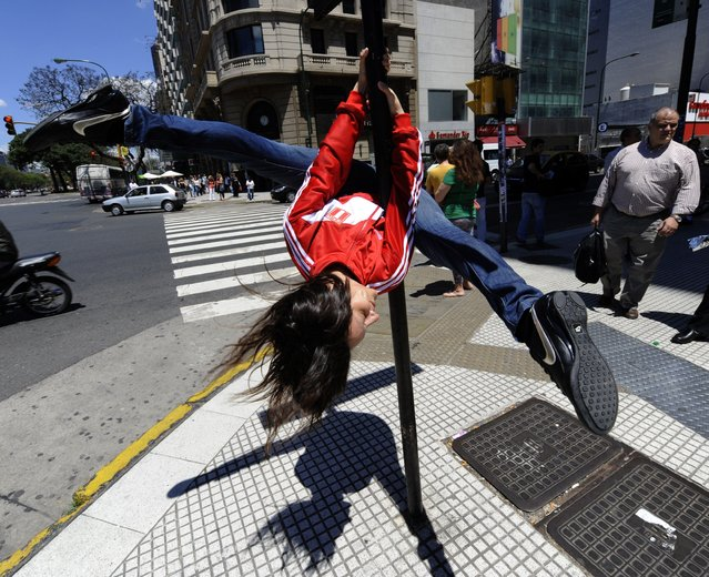 A Peruvian competitor of the Miss Pole Dance Sudamerica 2010, performs in front of the Obelisk, in downtown Buenos Aires on November 5, 2010, on the eve of the competition to be held in the city. The pole dance, born in night clubs in London, gradually grew and developed outside the field of sexuality and eroticism, as one of the most effective and fun activities when choosing a physical training routine. (Photo by Juan Mabromata/AFP Photo)