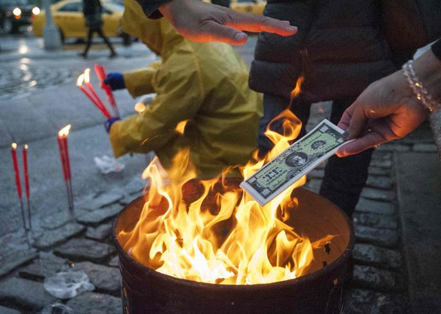 Buddhist mourners burn fake money during a candlelight vigil for slain New York Police Department (NYPD) officer Wenjian Liu one day ahead of his funeral in Manhattan, New York January 3, 2015. Liu, 32, and his partner Rafael Ramos, 40, were shot to death on December 20, 2014 as they sat in their squad car in Brooklyn. (Photo by Stephanie Keith/Reuters)