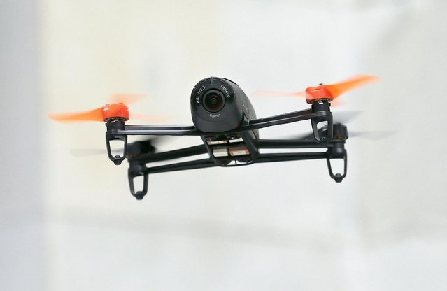 In this May 8, 2014 file photo, a Parrot Bebop drone flies during a demonstration event in San Francisco. The government is issuing the first two permits to agriculture and real estate companies to monitor crops and photograph properties for sale. (Photo by Jeff Chiu/AP Photo)