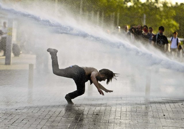 A man falls as riot police use tear gas and pressurized water to quash a peaceful demonstration by hundreds of people staging a sit-in protest to prevent the demolition of trees at an Istanbul park, on May 31, 2013. (Photo by Associated Press)