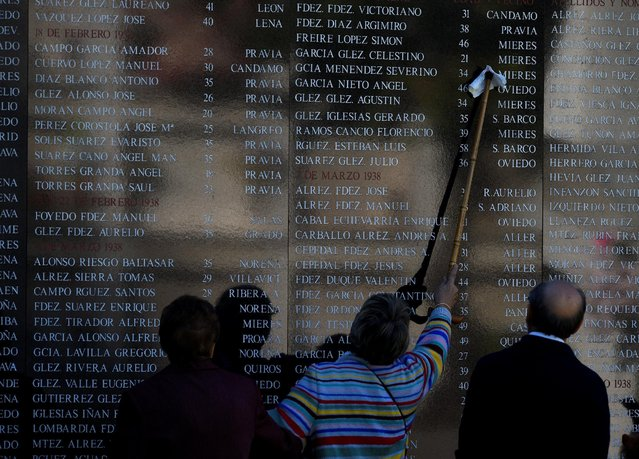 A woman cleans a name on the wall of a memorial grave for Republicans killed during and after the 1936-1939 Spanish civil war at cemetery of San Salvador on the eve of All Saints' Day in Oviedo, northern Spain, October 31, 2016. (Photo by Eloy Alonso/Reuters)