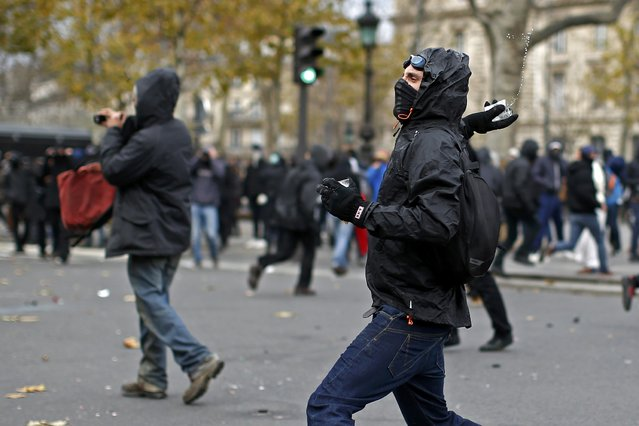A demonstrator throws a projectile at French CRS riot police during clashes at the Place de la Republique after the cancellation of a planned climate march following shootings in the French capital, ahead of the World Climate Change Conference 2015 (COP21), in Paris, France, November 29, 2015. (Photo by Benoit Tessier/Reuters)