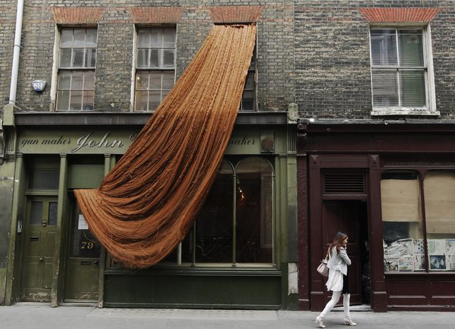 Hundreds of meters of dolls' hair cascades from the window of the Riflemaker gallery, part of an installation by French/Algerian artist Alice Anderson in London April 16, 2010. (Photo by Luke MacGregor/Reuters)