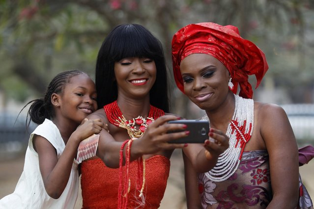 Models take selfies as they display neck beads, popularly used in social ceremonies, at a park in Ikeja duistrict in Lagos January 11, 2015. (Photo by Akintunde Akinleye/Reuters)