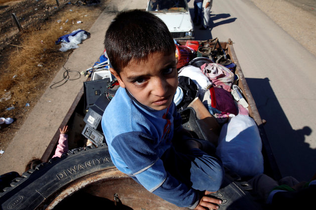 A displaced Iraqi child flees with his family during a battle with Islamic State militants in Kokjali village near Mosul, Iraq November 3, 2016. (Photo by Ahmed Jadallah/Reuters)