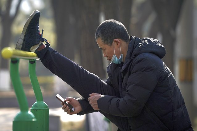 A man wearing a face mask to help curb the spread of the coronavirus browses his smartphone while stretching his leg at a public park in Beijing, Tuesday, January 26, 2021. Countries must cooperate more closely in fighting the challenges of the pandemic and climate change and in supporting a sustainable global economic recovery, Chinese President Xi Jinping said on Monday in an address to the World Economic Forum. (Photo by Andy Wong/AP Photo)
