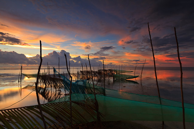 """Dusk at Patar Beach"". Fishnets strung out from the beach towards the sea at the village of Patar in Bolinao town, Pangasinan. Location: Bolinao, Pangasinan, Philippines. (Photo and caption by Hilario Marbella/National Geographic Traveler Photo Contest)"