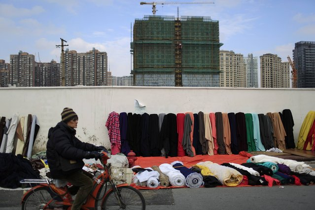 A man rides a motorcycle past textiles at a fabric stall in central Shanghai, January 20, 2015. (Photo by Aly Song/Reuters)