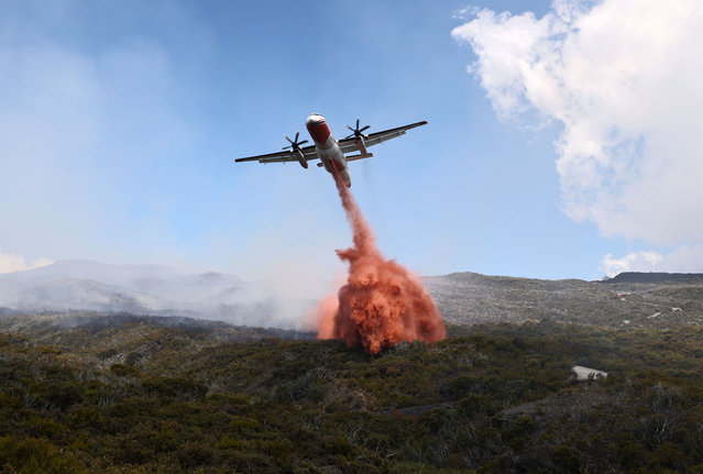 A water bomber aircraft fights a fire near Saint-Paul, on the French Indian Ocean island of La Reunion, on November 7, 2020. A fire, going on for three days in Reunion Island, has so far ravaged more than 200 hectares of vegetation in the Maido massif, a reservoir of biodiversity in the west of the island. (Photo by Richard Bouhet/AFP Photo)