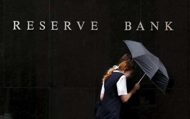 People walk past the Reserve Bank of Australia (RBA) building during rainy weather in central Sydney in this December 1, 2009 file photo.  Central banks in Australia and New Zealand will likely greet the Fed rate hike with relief as the U.S climbs. (Photo by Daniel Munoz/Reuters)