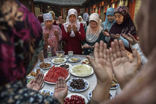 Women from the Hui Muslim community pray over food before breaking their fast during the holy fasting month of Ramadan at the Nanxiapo Mosque on June 8, 2018 in Beijing, China. Islam in China dates back to the 10th century as the legacy of Arab traders who  ventured from the Middle East along the ancient Silk Road. Of an estimated 23 million Muslims in China, roughly half are Hui, who are ethnically Chinese and speak Mandarin. China's constitution provides for Islam as one of five 'approved' religions in the officially atheist country though the government enforces severe limits. Worship is permitted only at state-sanctioned mosques and proselytizing in public is illegal. The Hui, one of 55 ethnic minorities in China (along with the Han majority), have long nurtured a coexistence with the Communist Party and is among the minority groups with political representation at various levels of government. The Hui Muslim population fast from dawn until dusk during Ramadan and it is believed there are more than 20 million members of the community in the country. (Photo by Kevin Frayer/Getty Images)