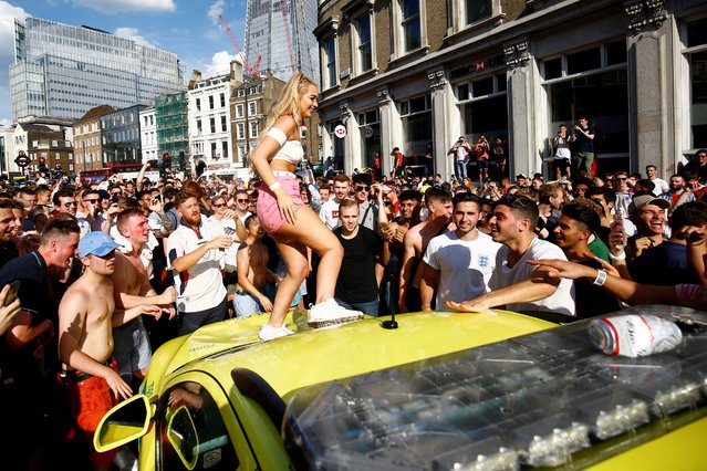 England fan celebrates on top of an ambulance after England' s win over Sweden in the Russia 2018 World Cup quarter- final football match, in London on July 7, 2018. (Photo by Henry Nicholls/Reuters)