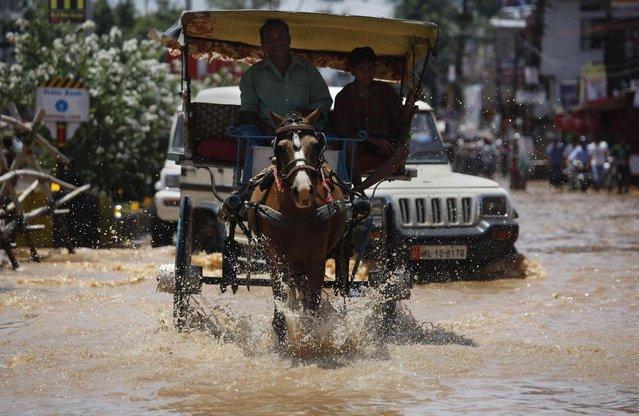A man rides a horse cart through a flooded street in Gauhati, India, Tuesday, July 16, 2013. (Photo by Anupam Nath/AP Photo)