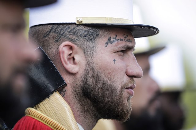 """A member of the 2e Regiment Etranger d'Infanterie de la Legion Etrangere (2nd Foreign Infantry Regiment) wears a tattoo with the legion's motto """"March or Die"""" (Marche ou Creve) as he takes part in the annual Bastille Day military parade on the Champs-Elysees avenue in Paris on July 14, 2018. (Photo by Thomas Samson/AFP Photo)"""