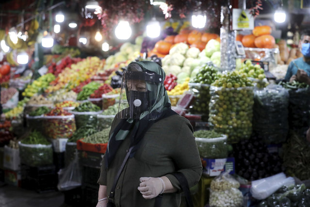 A woman wearing a protective face mask and gloves to help prevent the spread of the coronavirus walks through the Tajrish traditional bazaar in northern Tehran, Iran, Thursday, October 15, 2020. Eight months after the pandemic first stormed Iran, pummeling its already weakened economy and sickening officials at the highest levels of its government, authorities appear just as helpless to prevent its spread. (Photo by Ebrahim Noroozi/AP Photo)