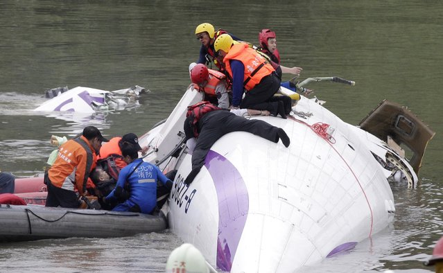 Rescuers pull a passenger out of the TransAsia Airways plane which crash landed in a river in New Taipei City, February 4, 2015. (Photo by Pichi Chuang/Reuters)