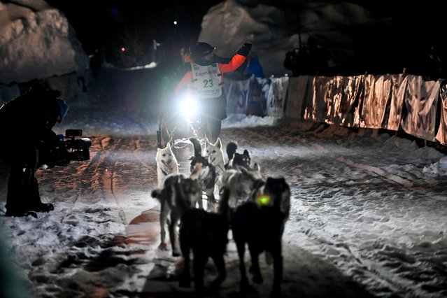 Dallas Seavey's team runs into the chute at the finish line to win his fifth Iditarod Dog Sled Race at Deshka Landing near Willow, Alaska, March 15, 2021. Seavey, 34, completed this year's race in seven days, 14 hours and 8:57 minutes. In 2012, he became the youngest Iditarod champion. The third-generation Iditarod musher has now tied Rick Swenson for the most victories. He was greeted at the finish line by his father, three-time champion Mitch Seavey, and will pocket about $40,000 in prize money. (Photo by Marc Lester/ADN/Pool via Reuters)