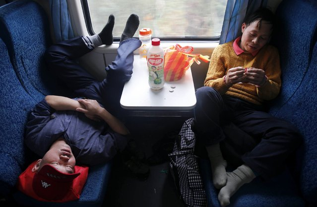 A passenger sleeps in his seat on board a train, that has been set aside exclusively for migrant workers travelling from Guangzhou of Guangdong province to Wuhan of Hubei province, February 7, 2015. (Photo by Reuters/Stringer)