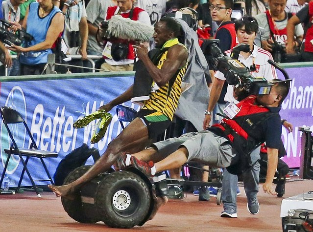 Usain Bolt of Jamaica is hit by a cameraman on a Segway as he celebrates after winning the men's 200 metres final at the 15th IAAF World Championships at the National Stadium in Beijing, China, August 27, 2015. (Photo by Reuters/Stringer)