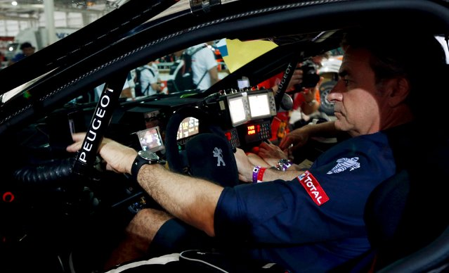 Peugeot driver Carlos Sainz of Spain sits inside his car at the technical verification area ahead of the Dakar Rally 2016 in Buenos Aires, Argentina, January 1, 2016. (Photo by Marcos Brindicci/Reuters)