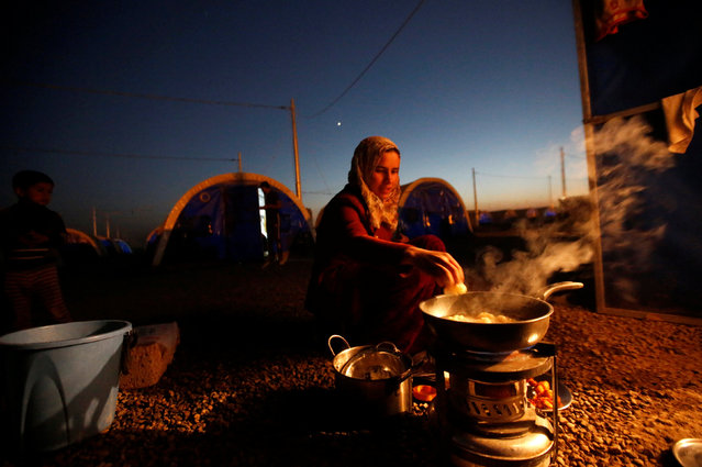 A displaced Iraqi woman, who fled the Islamic State stronghold of Mosul, prepares dinner for her family outside their tent at Khazer camp, Iraq November 28, 2016. (Photo by Mohammed Salem/Reuters)