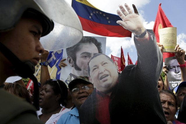 Supporters of Venezuela's President Nicolas Maduro gather outside Supreme Court building next to a cardboard cut-out of  Venezuela's late President Hugo Chavez in Caracas, January 7, 2016. (Photo by Marco Bello/Reuters)