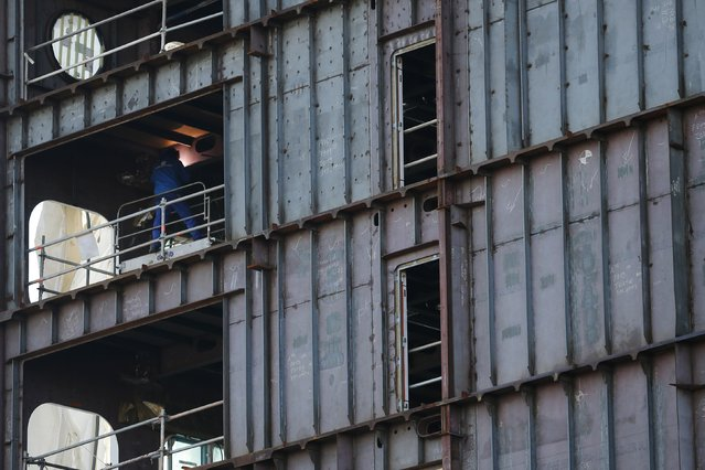 A ship builder works on a section of the Oasis Class 3 cruise ship under construction at the STX Les Chantiers de l'Atlantique shipyard site in Saint-Nazaire, western France, February 17, 2015. (Photo by Stephane Mahe/Reuters)