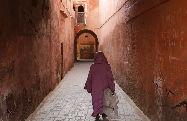 A woman, wearing traditional clothing, walks along the old Medina in the city of Marrakech December 13, 2014. (Photo by Youssef Boudlal/Reuters)