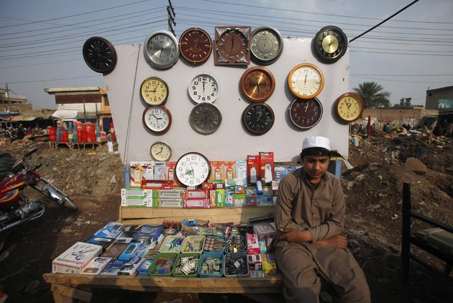 Muhammad Ahmad, an Afghan refugee, whose family have a residency card which will expire on December 2015, waits for customers while selling wall clocks and general items from his makeshift stall on the outskirts of Peshawar February 18, 2015. (Photo by Fayaz Aziz/Reuters)
