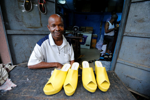 Boniface, a shoemaker, poses for a photograph with a set of finished women's shoes at a shoe factory in Araria market in Aba, Nigeria August 19, 2016. (Photo by Afolabi Sotunde/Reuters)