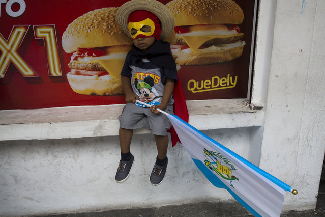 A boy in costume clutching a Guatemalan flag sits outside a local fast food restaurant as he waits with his father for a march to start against Guatemalan President Jimmy Morales and corruption in Guatemala City, Thursday, September 20, 2018. Thousands marched to protest Morales' decision to end the work of a U.N. anti-corruption commission that has helped lead high-profile graft probes targeting dozens of powerful people, including one involving Morales. (Photo by Moises Castillo/AP Photo)