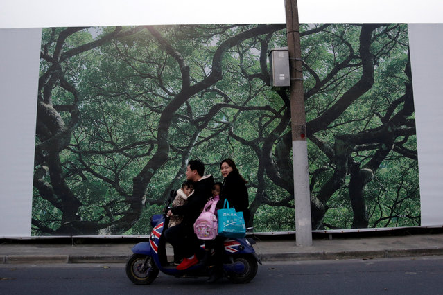 A family rides an electric scooter on a street in Shanghai, China December 1, 2016. (Photo by Aly Song/Reuters)