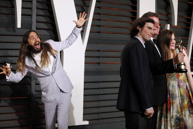 "Actor Jared Leto photobombs producer James W. Skotchdopole with this Best Picture award for the film ""Birdman"" and his guests at the 2015 Vanity Fair Oscar Party in Beverly Hills, California February 22, 2015. (Photo by Danny Moloshok/Reuters)"
