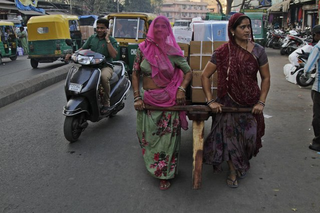 Indian women laborers pull a hand cart loaded with goods at a market in Ahmadabad, India, Monday, February 23, 2015. The government of Asia's third-largest economy is this week expected to present in Parliament the budget for the fiscal year ending March 2016. (Photo by Ajit Solanki/AP Photo)