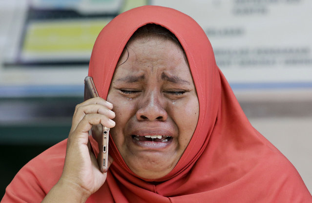 A woman cries as she uses the recovered mobile phone of her daughter who was killed in the massive earthquake at Palu, Central Sulawesi, Indonesia Thursday, October 4, 2018. The mother did not get the chance to see the body of her daughter after she was buried earlier in a mass grave. Life is on hold for thousands living in tents and shelters in the Indonesian city hit by a powerful earthquake and tsunami, unsure when they'll be able to rebuild and spending hours each day often futilely trying to secure necessities such as fuel for generators. (Photo by Aaron Favila/AP Photo)