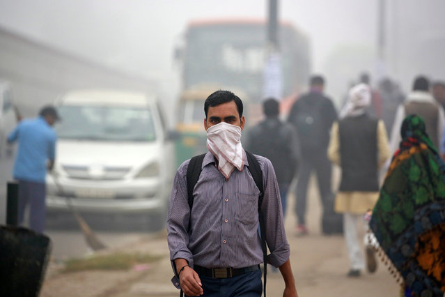 A man covers his face with a handkerchief during heavy fog in Delhi, India December 1, 2016. (Photo by Cathal McNaughton/Reuters)
