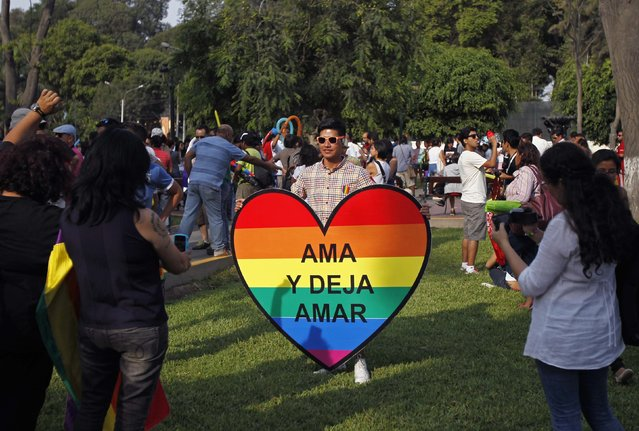 "Members of gay and lesbian organizations take pictures before a march in support of the Civil Union project law in Lima, March 7, 2015. The banner reads: ""Love and let love"". REUTERS/Enrique Castro-Mendivil (PERU - Tags: POLITICS SOCIETY)"