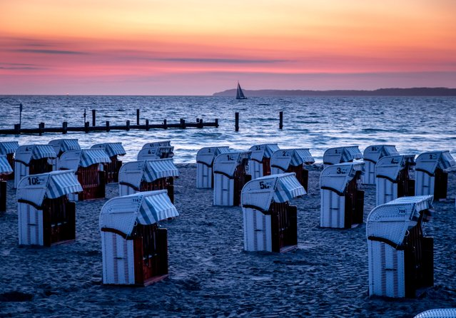 Beach chairs are lined up at the Baltic Sea in Travemuende, northern Germany, before sunrise on Sunday, April 18, 2021. (Photo by Michael Probst/AP Photo)