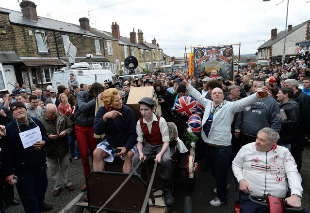 Essay Finalist – John Giles. A horse drawn hearse carrying an effigy and a coffin pass Goldthorpe Union Jack Memorial club on the day  of former Prime Minister Margaret Thatchers Funeral, April 17,  2013. (Photo by John Giles/PA Wire)